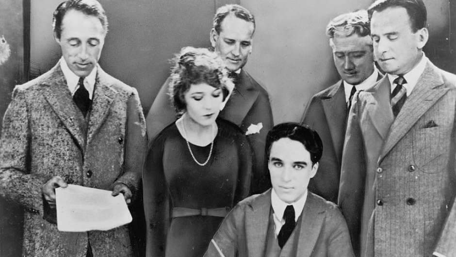 Fotomontage: D. W. Griffith, Mary Pickford, Charlie Chaplin, Douglas Fairbanks und Anwälte bei der Unterzeichnung des Gründungsvertrags von United Artists